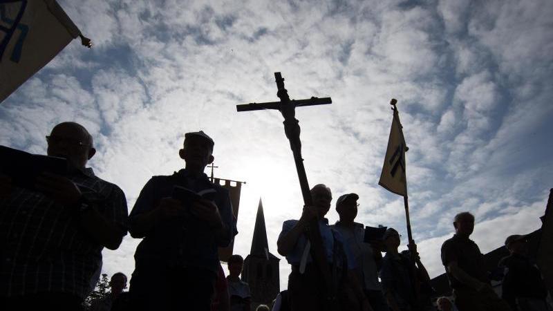 Pilger der 166. Telgter Wallfahrt laufen im Gegenlicht auf einer Straße und halten ein Kreuz. Foto: Friso Gentsch/dpa/Archivbild