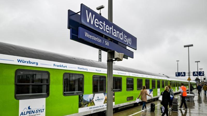 Fahrgäste des neuen Alpen-Sylt-Nachtexpress von Sylt nach Salzburg laufen über den Bahnsteig. Foto: Axel Heimken/dpa
