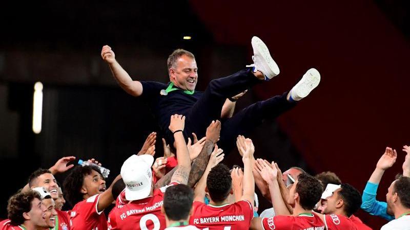 Münchens Trainer Hansi Flick (M) wird von seinen Spielern nach dem Sieg in die Luft geworfen. Foto: Robert Michael/dpa-Zentralbild/Pool/dpa/Archivbild