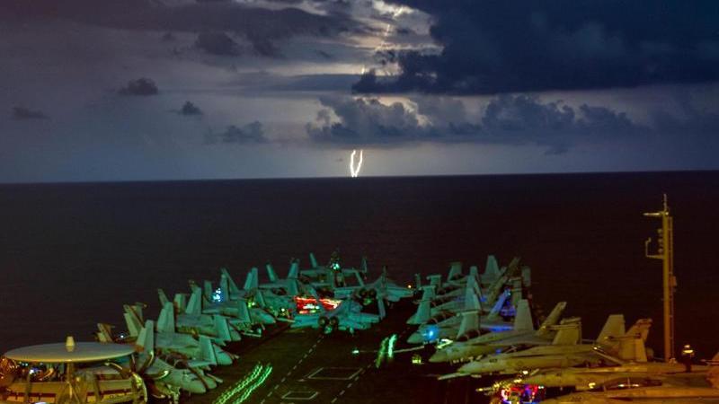 """Militärjets stehen auf dem Flugdeck des Flugzeugträgers USS Nimitz (CVN 68) im Südchinesischen Meer während eines Gewitters. Die """"USS Nimitz"""" und die """"USS Ronald Reagan"""" führen als Nimitz Carrier Strike Force Dual Carrier-Operationen im Südchinesischen Me"""