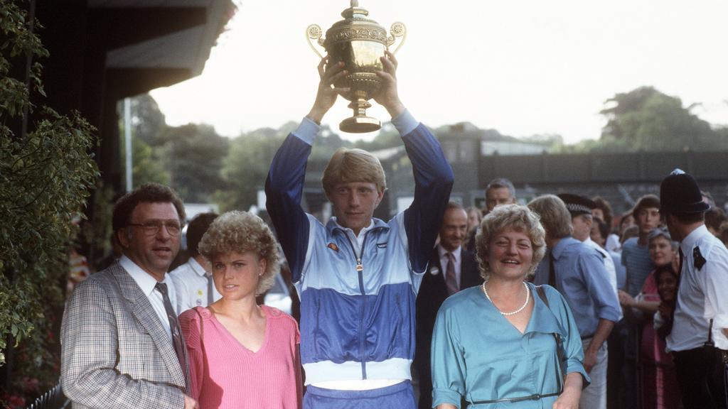 Boris Becker verläßt mit erhobenem Pokal im Kreis seiner Familie nach seinem Sieg den Center-Court in Wimbledon. Rechts seine Mutter Elvira, links Vater Karl-Heinz und Schwester Sabine. Der 17-jährige, ungesetzte Tennisspieler aus Leimen gewann als j