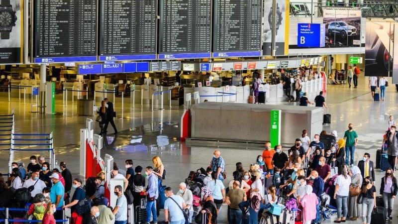 Reisende stehen in der Abflughalle im Terminal 1 am Flughafen Frankfurt. Hier herrscht noch immer deutlich weniger Betrieb als in Vor-Corona-Zeiten. Foto: Andreas Arnold/dpa