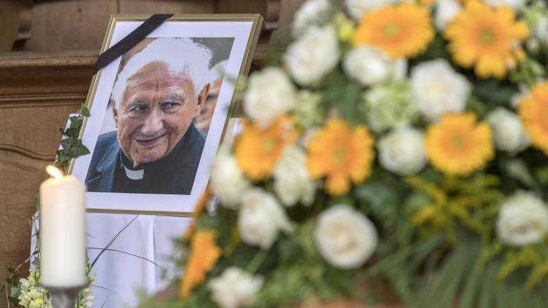 Ein Foto von Domkapellmeister Georg Ratzinger steht im Dom neben seinem Sarg. Foto: Uwe Moosburger/Bistum Regensburg/dpa/Archivbild