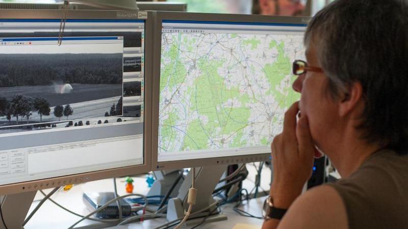 Eine speziell geschulte Forstwirtinblickt in Lüneburg (Niedersachsen) auf Monitore und wertet Bilder der insgesamt 20 Waldbrandüberwachungskameras aus sechs Landkreisen aus. Foto: picture alliance / dpa/Archiv