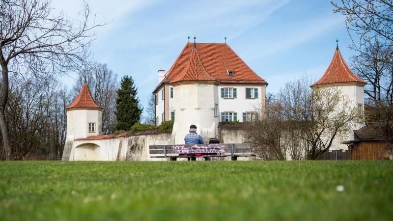 Ein Mann sitzt bei sonnigem Wetter vor dem Schloss Blutenburg. Foto: Lino Mirgeler/dpa/Symbolbild