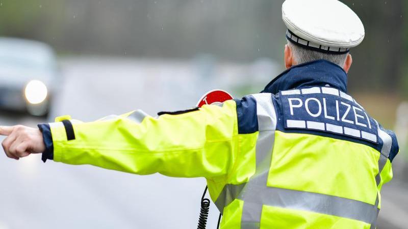 Ein Polizist bei einer Geschwindigkeitskontrolle an einer Bundesstraße. Foto: Uwe Anspach/dpa