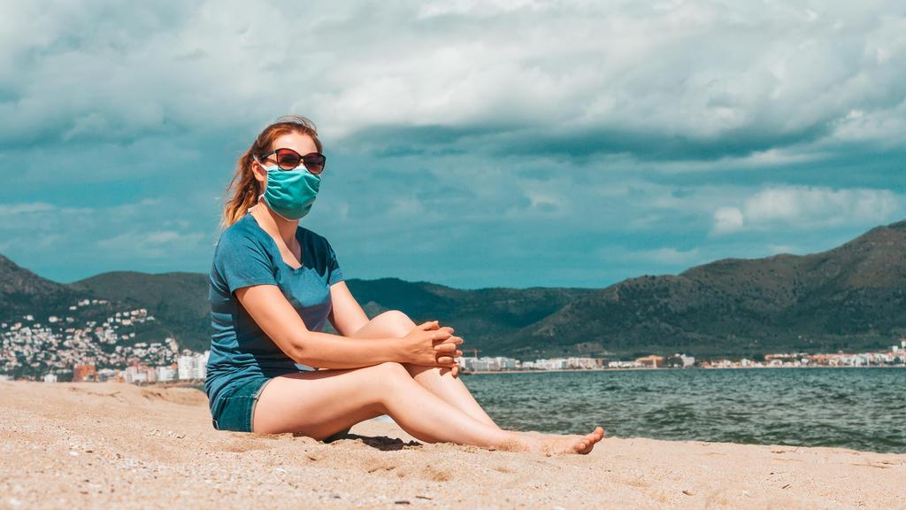 Frau mit Maske sitzt am Strand