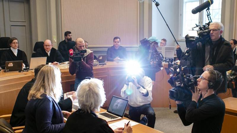 Die Angeklagte (2.v.r) wird von Medienvertretern fotografiert und gefilmt. Foto: Frank Molter/dpa/Archivbild