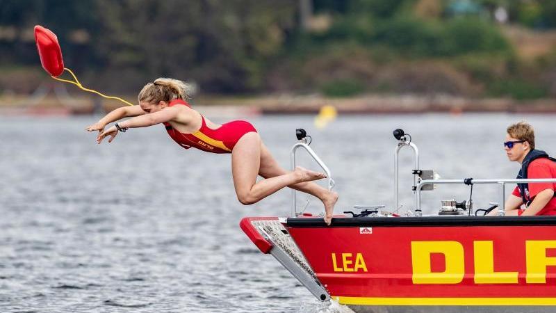 Eine Rettungsschwimmerin der DLRG springt während einer Übung in einen See. Foto: Marcel Kusch/dpa/Symbolbild