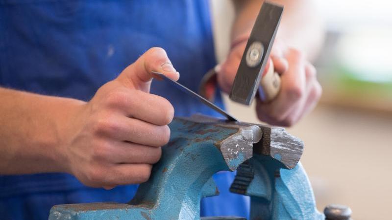 Ein Auszubildender steht mit einem Hammer an einem Schraubstock. Foto: Sebastian Kahnert/dpa-Zentralbild/dpa/Archivbild