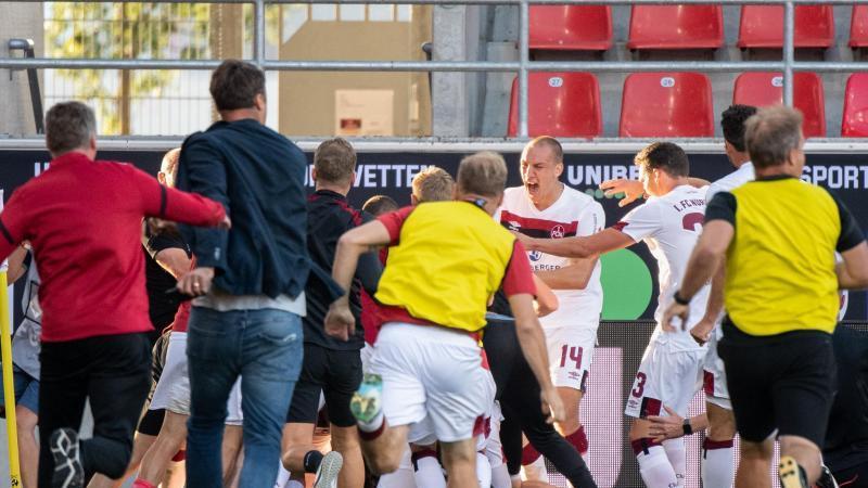 Das Team des 1. FC Nürnberg jubelt über den erlösenden Treffer zum 3:1. Foto: Matthias Balk/dpa