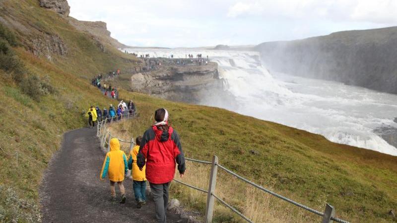 Touristen wandern zum Wasserfall Gullfoss. Foto: Steffen Trumpf/dpa