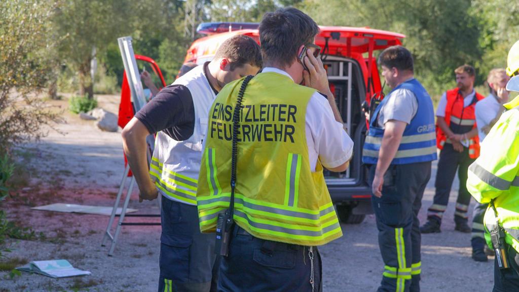 12.07.2020, Baden-Württemberg, Karlsruhe: Einsatzkräfte der Feuerwehr stehen mit Fahrzeugen auf einem Waldparkplatz. Ein Ultraleichtflugzeug mit zwei Männern ist am Sonntagabend in einen Wald bei Rheinstetten abgestürzt. Die zwei Männer, die mit dem