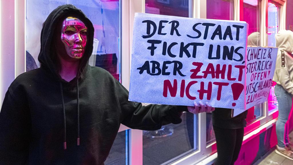 11.07.2020, Hamburg: Eine Prostituierte hält in der Herbertstraße ein Schild mit der Aufschrift «Der Staat fickt uns, aber er zahlt nicht». Sie demonstriert mit anderen Frauen für die Öffnung der Bordelle auf St. Pauli. Diese sind zur Eindämmung der