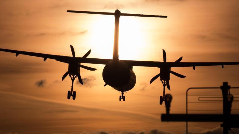 Ein Propellerflugzeug vor der Sonne. Foto: picture alliance / Daniel Karmann/dpa/Symbolbild