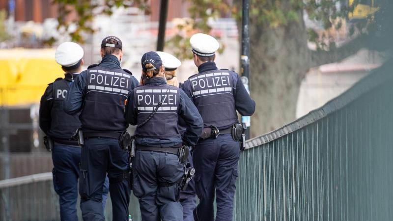 Polizeibeamte gehen durch die Innenstadt. Foto: Sebastian Gollnow/dpa/Symbolbild