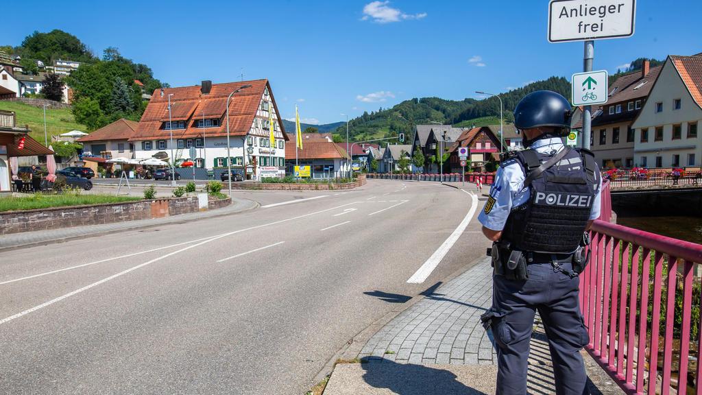Baden-Württemberg, Oppenau: Ein Polizist sichert eine Straße im Ortskern. Ein Großaufgebot der Polizei sucht seit dem Vormittag einen bewaffneten Mann.