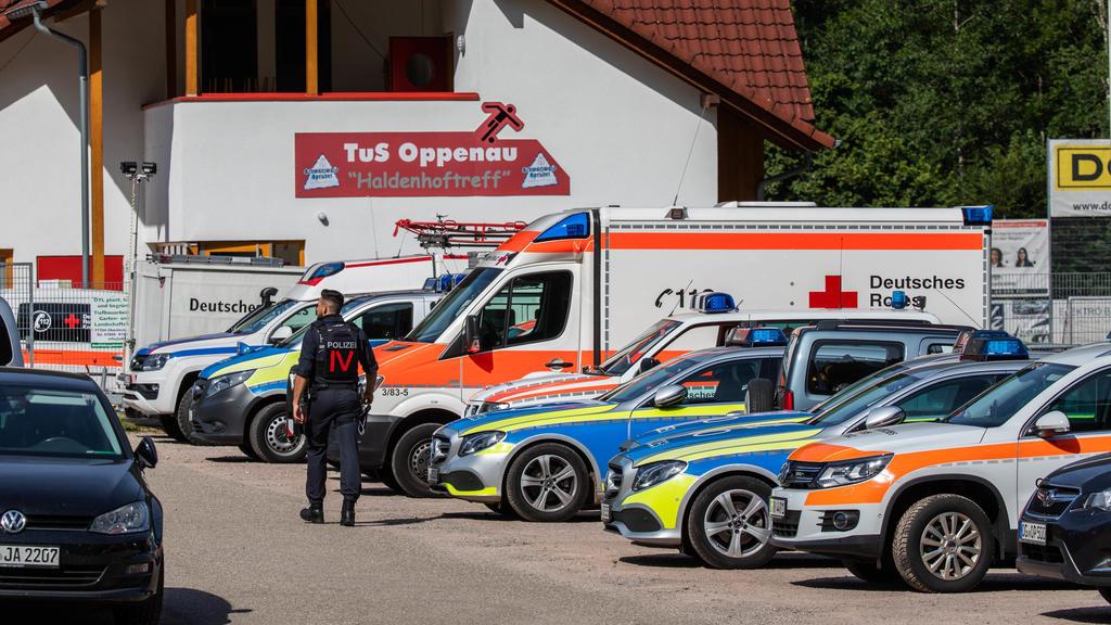 13.07.2020, Baden-Württemberg, Oppenau: Ein Polizist geht über den Parkplatz eines Sportlerheims, das Polizei und Rettungskräften als Sammelpunkt dient. Ein Großaufgebot der Polizei sucht seit dem Vormittag einen bewaffneten Mann, der während einer K