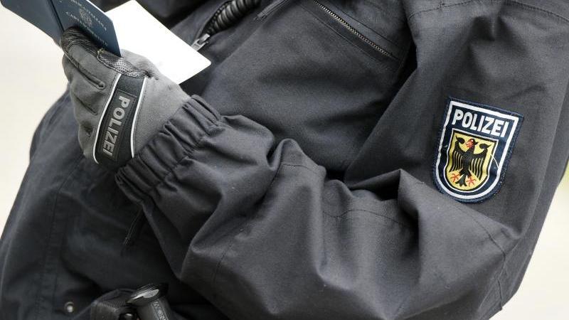 Ein Polizist überprüft Personalien. Beim Racial Profiling werden Menschen auf Grundlage von Stereotypen und äußerlichen Merkmalen als verdächtig eingestuft und überprüft. Foto: Felix Kästle/dpa