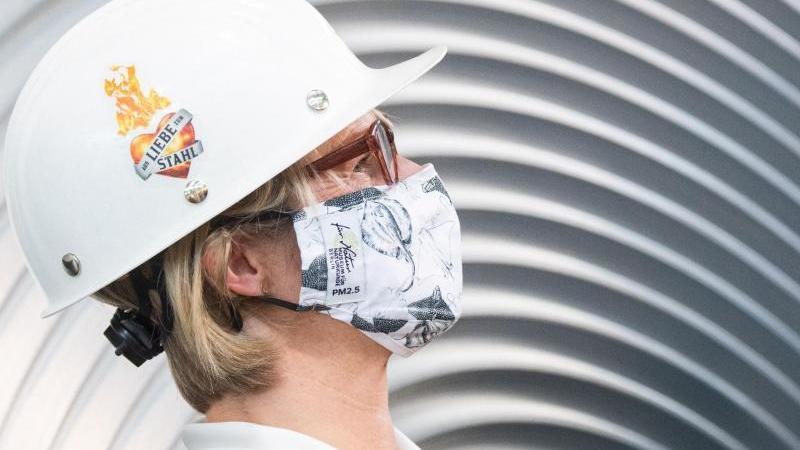 Anja Karliczek (CDU), Bundesministerin für Bildung und Forschung, trägt einen Mund-Nasen-Schutz und einen Helm im Werk der Salzgitter AG. Foto: Julian Stratenschulte/dpa