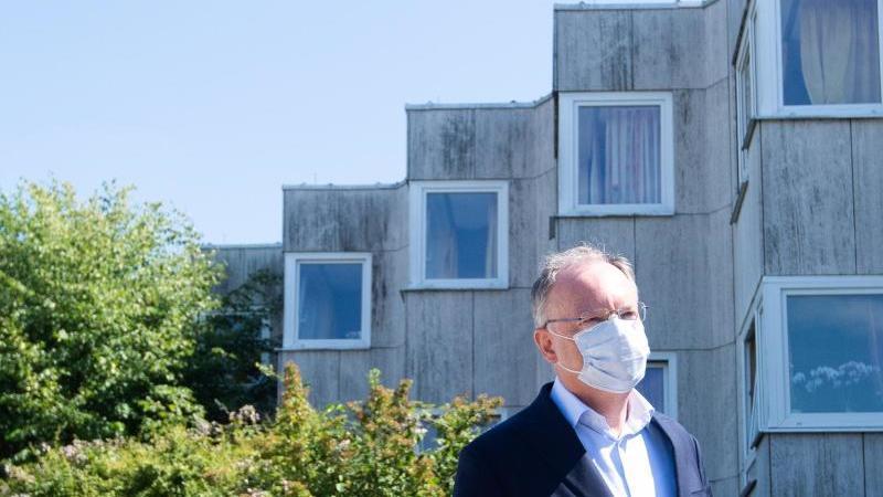 Stephan Weil (SPD) trägt einen Mund-Nasenschutz und steht vor dem Hanns-Lilje-Heim. Foto: Julian Stratenschulte/dpa