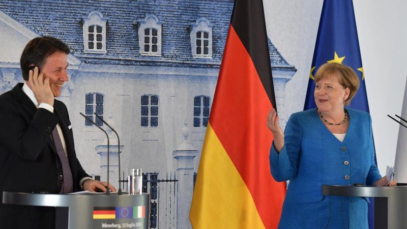 Bundeskanzlerin Angela Merkel (CDU) und Giuseppe Conte, Ministerpräsident von Italien, scherzen während einer Pressekonferenz auf Schloss Meseberg. Foto: Tobias Schwarz/AFP pool/dpa