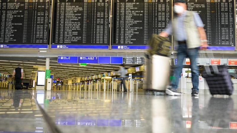 Reisende gehen mit Gepäck durch die Abflughalle im Terminal 1 am Flughafen. Foto: Andreas Arnold/dpa/Archivbild