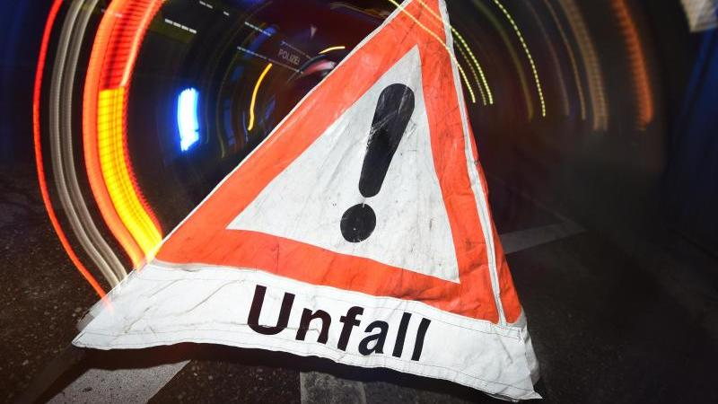 """Ein Warndreieck mit dem Schriftzug """"Unfall"""" steht vor einem Blaulicht auf der Straße. Foto: Patrick Seeger/dpa/Illustration"""
