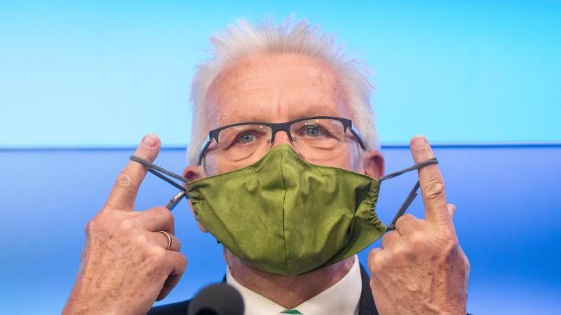 Winfried Kretschmann (Bündnis 90/Die Grünen) nimmt vor Beginn einer Pressekonferenz seine Schutzmaske ab. Foto: Christoph Schmidt/dpa/Archivbild