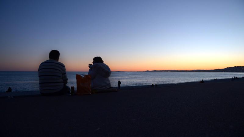 Ein Paar genießt am 22.02.2014 in Nizza (Frankreich) am Strand den Sonnenuntergang. Am Sonntag findet die Auslosung der Qualifikationsgruppen für die Fußball-EM 2016 in Frankreich statt. Erstmals nehmen 24 Mannschaften am Turnier teil. Foto: Federico