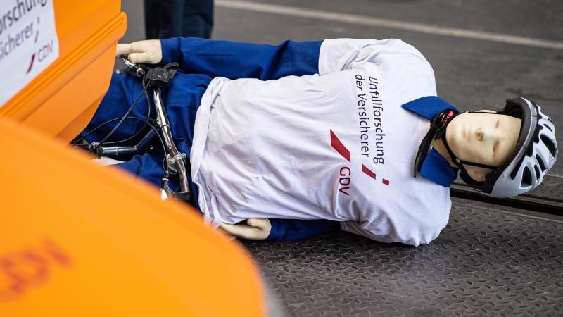 Bei einem Crashtest der Unfallforscher der Versicherer liegt ein Crashtest-Dummy mit seinem Fahrrad auf der Straße, nachdem er gegen eine geöffnete Tür eines geparkten Autos fuhr - einem sogenannten Dooring-Unfall. Foto: Guido Kirchner/dpa