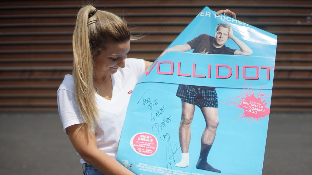 """Daria mit einem Poster, auf dem die Widmung """"Für die geile Daria"""" steht."""