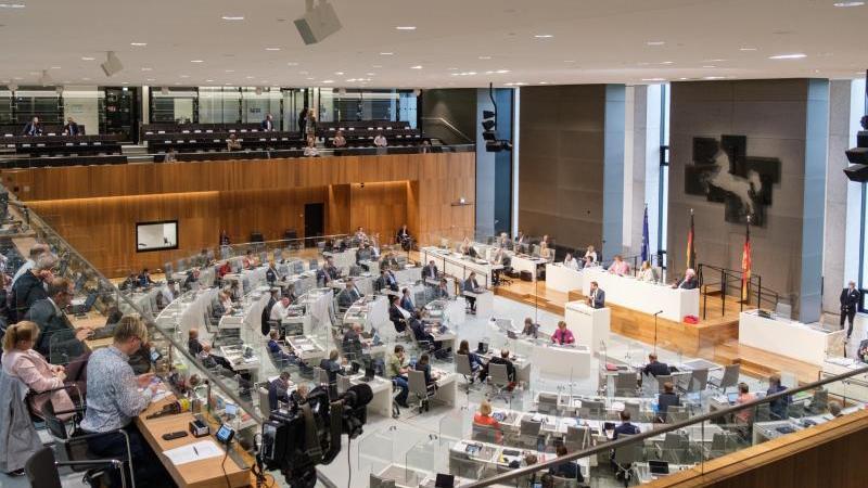 Abgeordnete und Journalisten sitzen hinter gläsernem Hygieneschutz im Landtag. Foto: Ole Spata/dpa/Archivbild