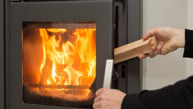 Ein Mann legt in seiner Wohnung ein Stück Holz in einen Kaminofen, in dem ein Feuer brennt. Foto: Silas Stein/dpa