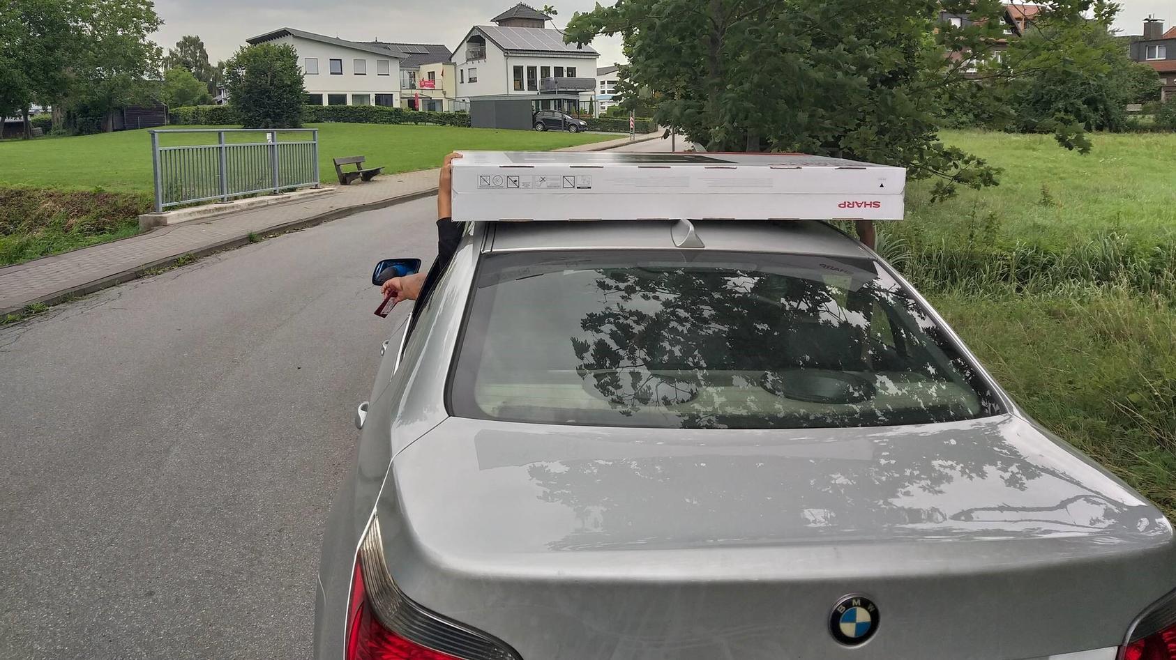 Skurriler Transport: Diese Eltern ließen ihre Kinder den Flachbildfernseher auf dem Autodach festhalten.