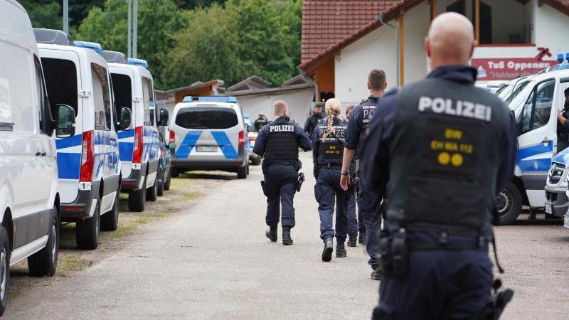 Polizisten gehen an einem Parkplatz in Oppenau an Polizeifahrzeugen vorbei. Foto: Benedikt Spether/dpa