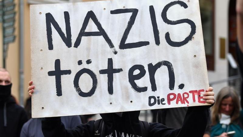 """Ein Demonstrant hält ein Schild mit der Aufschrift """"Nazis töten"""". Foto: Martin Schutt/dpa-Zentralbild/dpa"""