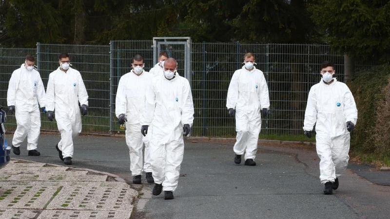 Bundeswehrsoldaten in Schutzanzügen und mit Mundschutz gehen über ein Gelände. Foto: Bodo Schackow/dpa-Zentralbild/dpa/Archivbild