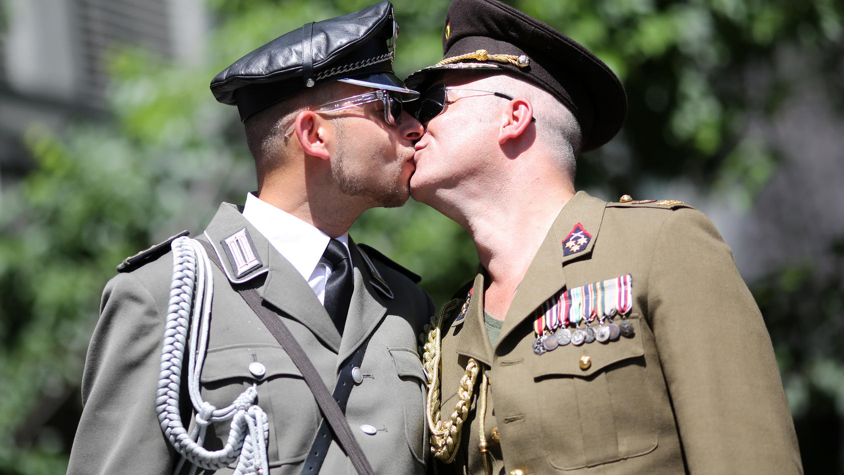 Symbolfoto: Zwei als Soldaten verkleidete Männer küssen sich auf dem Christopher Street Day (CSD) / Archivfiti vom 20. Juli 2013