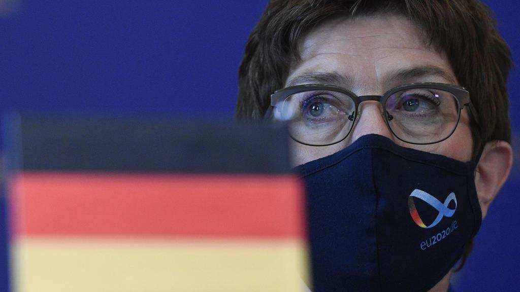 17.07.2020, Tschechien, Prag: Annegret Kramp-Karrenbauer (CDU), Bundesministerin der Verteidigung, sitzt mit Schutzmaske während einer Pressekonferenz nach ihrem Treffen mit dem tschechischen Verteidigungsminister Mtenar hinter einer kleinen Deutschl