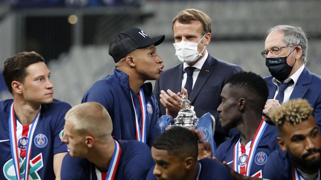 French President Emmanuel Macron, center, applauds as PSG's Kylian Mbappe, center left, walks past the trophy for the winners of the French Cup soccer final match between Paris Saint Germain and Saint Etienne at Stade de France stadium, in Saint Deni