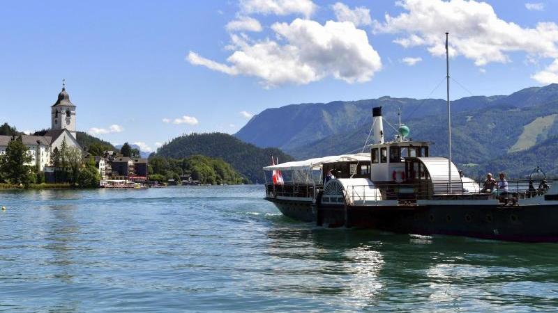 Ein Boot fährt über den Wolfgangsee. In der kleinen Gemeinde sind in den vergangenen Tagen mehr als 60 Corona-Tests positiv ausgefallen. Foto: Kerstin Joensson/AP/dpa