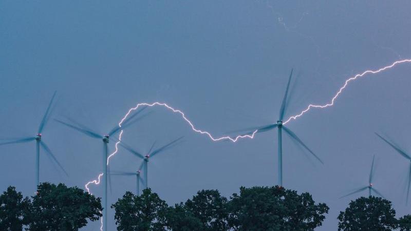 Ein Blitz erhellt den Abendhimmel über einer Landschaft mit Windenergieanlagen. Foto: Patrick Pleul/dpa-Zentralbild/dpa/Archiv/Symbolbild