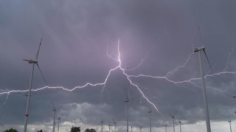 Blitze eines Gewitters leuchten über Windenergieanlagen. Foto: Patrick Pleul/dpa-Zentralbild/dpa/Archiv/Symbolbild