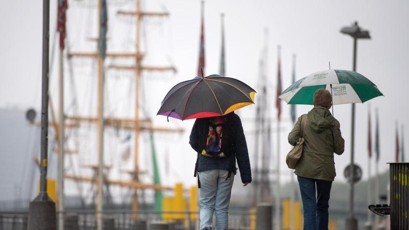 Spaziergänger mit Regenschirmen laufen an der Weserpromenade entlang. Foto: Sina Schuldt/dpa/Archivbild
