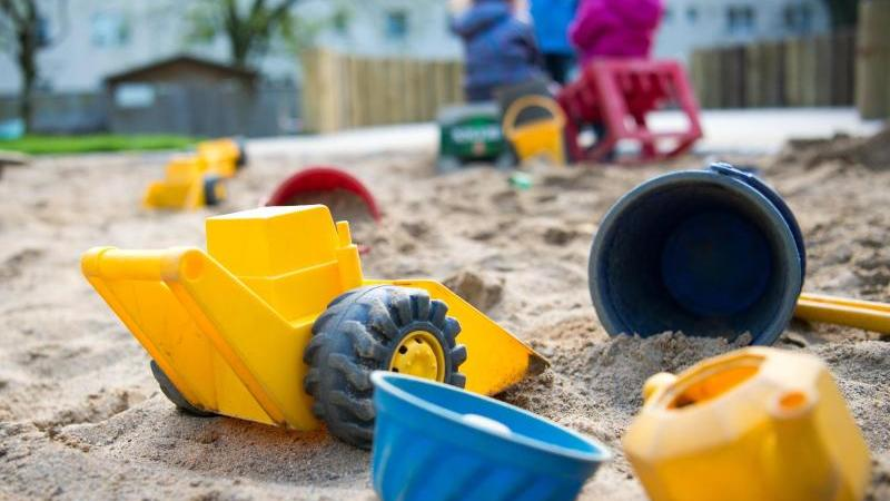 Spielzeug liegt in einem Sandkasten während Kinder spielen in einer Kindertagesstätte. Foto: Monika Skolimowska/dpa/Archivbild