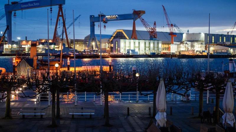 Das beleuchtete Werftgelände von ThyssenKrupp Marine Systems am Ufer der Förde ist vor Sonnenaufgang zu sehen. Foto: Gregor Fischer/dpa/Archivbild