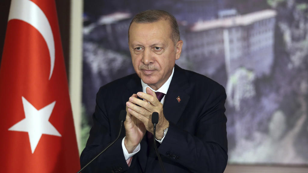 Turkey's President Recep Tayyip Erdogan applauds during a conference in Istanbul, Tuesday, July 28, 2020. Turkish lawmakers were making their final speeches Tuesday before voting on a bill that would give the government greater powers to regulate soc
