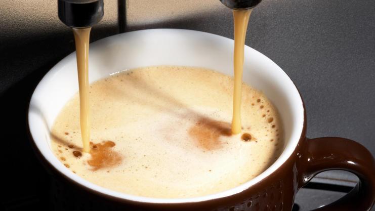 Kaffee läuft aus einer Maschine in eine Tasse.