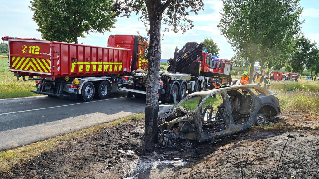 28.07.2020, Brandenburg, Groß Kreutz: Das ausgebrannte Unfallwrack eines Autos steht an einem Baum. Eine junge Fahrerin ist in Groß Kreutz bei Potsdam mit dem Auto gegen einen Baum geprallt und darin verbrannt. Es sei schwierig gewesen, die Frau in d